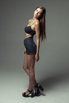Modelowe testy młodej ładnej dziewczyny na szaro