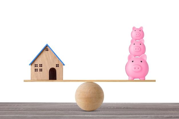 Modelowy dom na drewnianej huśtawce równoważący z układaniem oszczędności skarbonki na białym tle