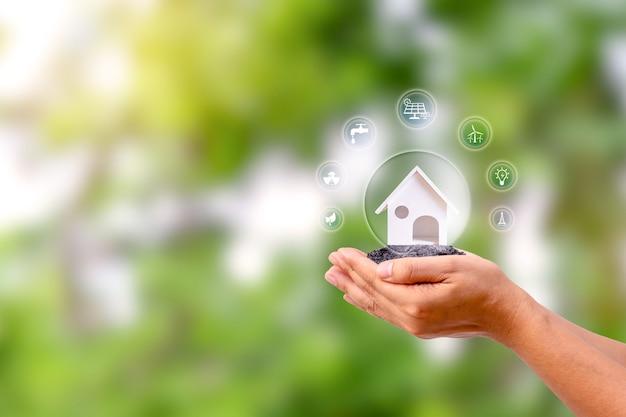 Modelowy dom z ikoną energii w ludzkiej dłoni, energooszczędna i przyjazna energetycznie koncepcja domu gibraltar