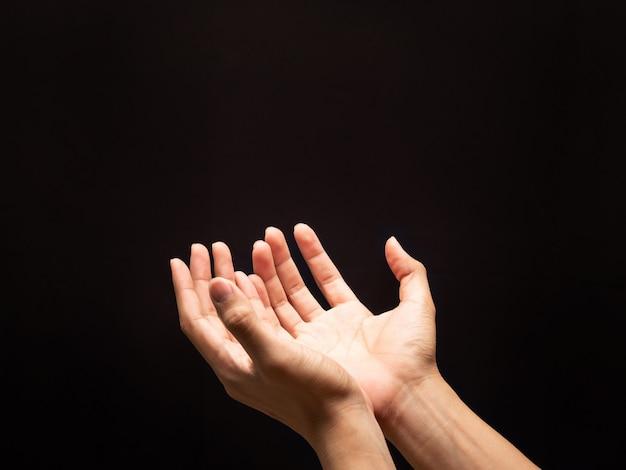 Modląc ręce na ciemnym tle z wiarą w religię i wiarę w boga.