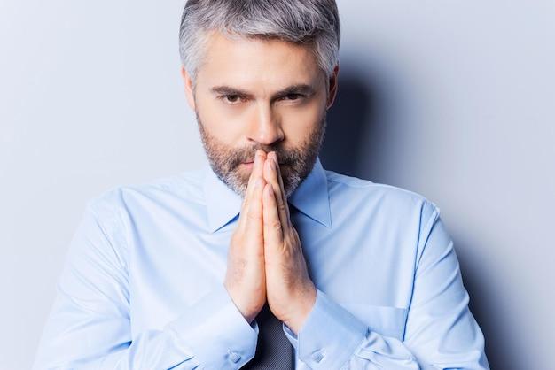 Modląc się o sukces. skoncentrowany dojrzały mężczyzna w koszuli i krawacie, trzymający się za ręce splecione przy twarzy i odwracający wzrok, stojąc na szarym tle