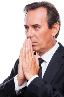 Modląc się o sukces w biznesie. widok z boku rozważnego dojrzałego mężczyzny w formalwear, trzymającego ręce splecione w pobliżu twarzy i odwracającego wzrok, stojąc na białym tle