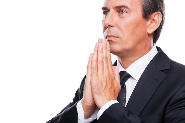 Modląc się o sukces. widok z boku rozważnego dojrzałego mężczyzny w formalwear, trzymającego ręce splecione w pobliżu twarzy i odwracającego wzrok, stojąc na białym tle