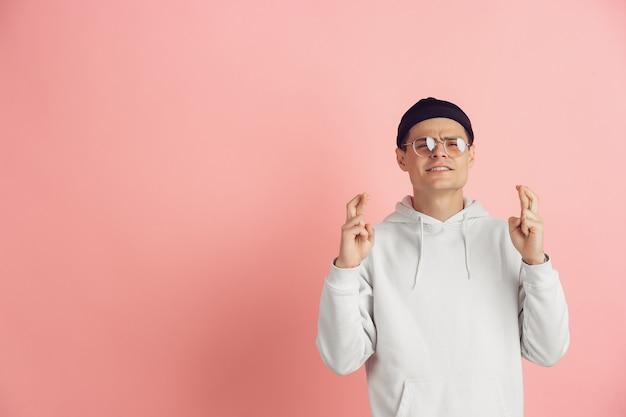 Modląc się o szczęście. kaukaski nowoczesny portret młodego człowieka na białym tle na różowym tle studio. piękny męski model w kolorze białym. pojęcie ludzkich emocji, wyraz twarzy, sprzedaż, reklama. miejsce.