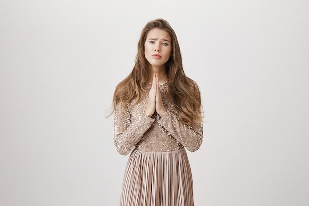 Modląca się dziewczyna błagająca o pomoc, załóż suknię wieczorową