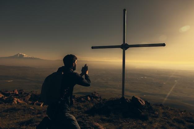 Modlący się człowiek i krzyż w górach