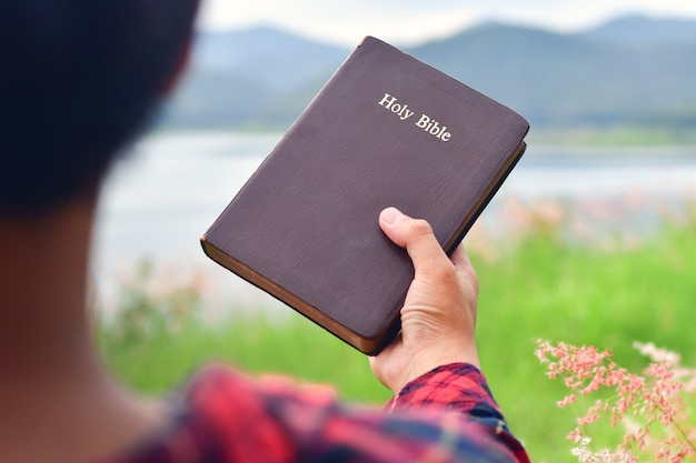 Modlący się mężczyzna trzyma świętą biblię. koncepcja chrześcijańska.