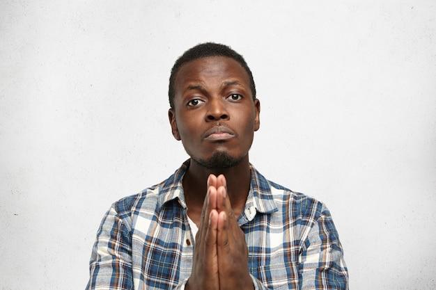 Modlący się młody afroamerykański mężczyzna ściskający ręce razem, wyglądający na winnego