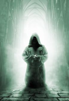 Modlący się średniowieczny mnich w ciemnym korytarzu świątyni