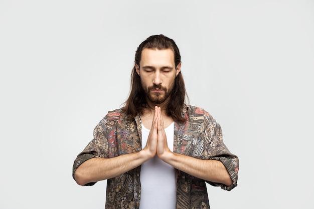 Modlitwa gestem ręki, prosi o coś więcej mocy, nadziei i wdzięczności. modnisia podróżnika elegancki beztroski mężczyzna na białym pracownianym tle, ludzie stylów życia