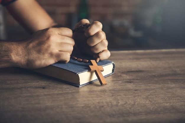 Modlitwa I Drewniany Krzyż Na Biblii Na Stole Premium Zdjęcia