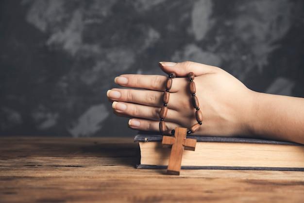 Modlitwa kobieta trzyma krzyż na biblii