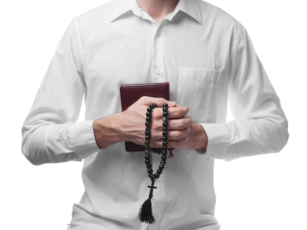 Modlitwa męska w białej koszuli z biblią i koralikami na białym tle
