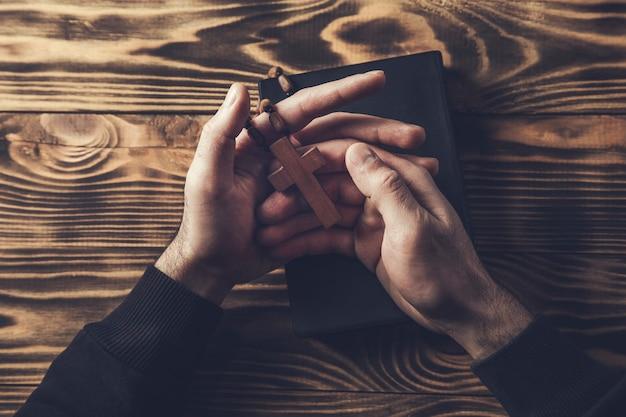 Modlitwa Mężczyzna Ręka Krzyż Na świętej Biblii Na Drewnianym Stole Premium Zdjęcia