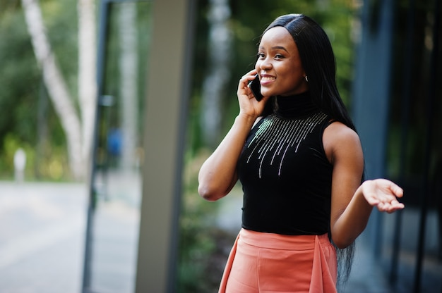 Modna afroamerykanka w brzoskwiniowych spodniach i czarnej bluzce rozmawia przez telefon na świeżym powietrzu.