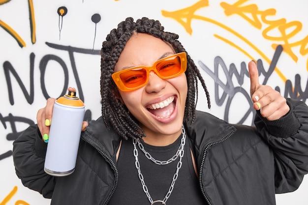 Modna afroamerykańska nastolatka uśmiecha się szeroko i wykonuje gesty w miejskim miejscu używa sprayu w aerozolu do rysowania graffiti, nosi okulary przeciwsłoneczne, a kurtka należy do gangu chuliganów
