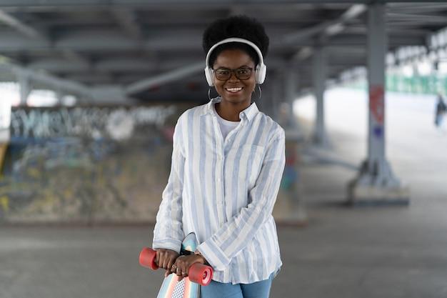 Modna afrykańska łyżwiarka w kosmosie do jazdy na deskorolce w bezprzewodowych słuchawkach i szczęśliwym uśmiechu