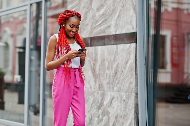 Modna amerykanin afrykańskiego pochodzenia dziewczyna przy różowymi spodniami i czerwonymi strachami pozuje na zewnątrz z telefonem komórkowym.
