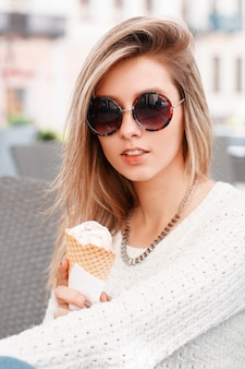 Modna atrakcyjna młoda hipster kobieta w stylowy sweter z dzianiny w modnych okularach przeciwsłonecznych z lodami w rękach siedzi w kawiarni w słoneczny wiosenny dzień. ładna dziewczyna blondynka.