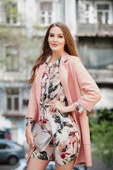 Modna atrakcyjna stylowa uśmiechnięta kobieta spaceru ulicą miasta w różowym płaszczu wiosenny trend w modzie trzymając torebkę