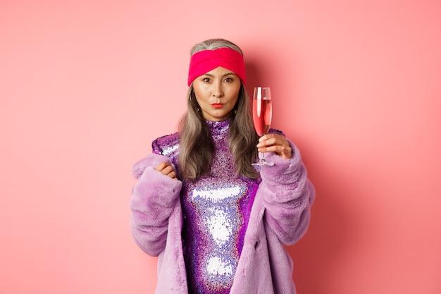 Modna azjatycka starsza modelka podnosząca kieliszek szampana, ubrana w modną brokatową sukienkę i sztuczne futro i patrząca w kamerę, gratulująca wakacyjnego, różowego tła