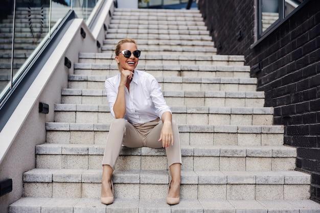 Modna bizneswoman siedzi na schodach przed centrum biznesowym i pozuje.
