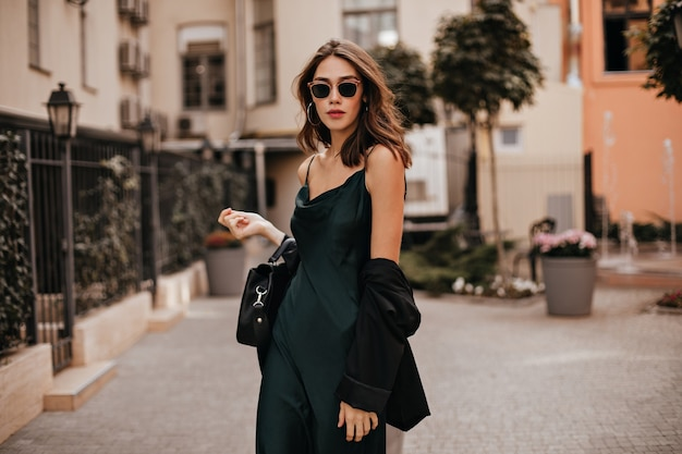 Modna blada brunetka w długiej zielonej sukience, czarnej kurtce i okularach przeciwsłonecznych, stojąca na ulicy w ciągu dnia przy ścianie jasnego budynku miejskiego