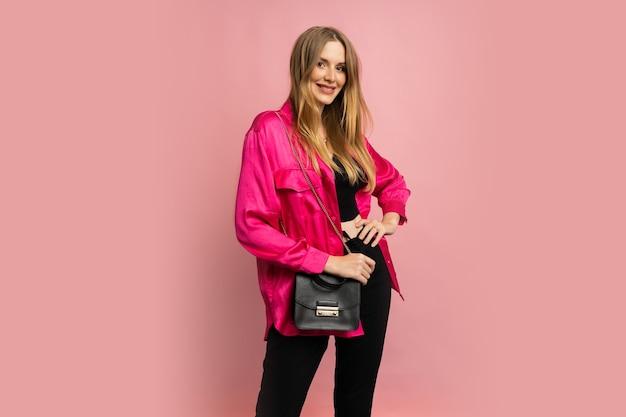Modna blond kobieta w stylowych letnich ubraniach pozuje na różowej ścianie