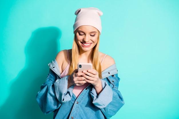 Modna blondynka pozowanie na niebieskiej ścianie