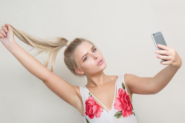 Modna blondynka robi selfie na telefonie komórkowym na szarym tle