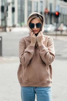Modna blondynka w brązowej bluzie oversize