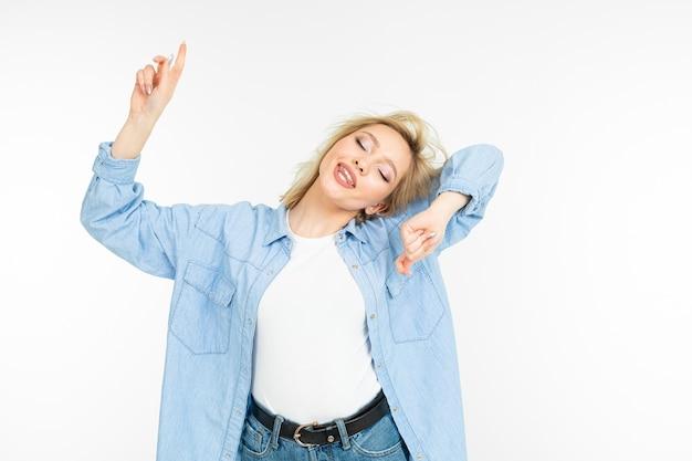 Modna blondynka w dżinsowej niebieskiej koszuli tańczy energicznie na tle białego studia.