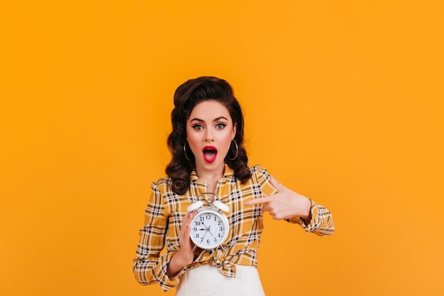 Modna brunetka dama pokazuje duży zegar. strzał studio dziewczyny w stroju vintage żółty.