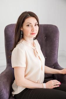 Modna brunetka dziewczyna w lekkiej bluzce siedzi na krześle, pozuje i patrzy w kamerę.