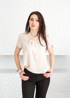 Modna brunetka dziewczyna w lekkiej bluzce stoi przy białej ścianie, pozuje i patrzy w kamerę