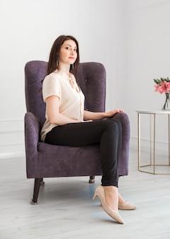 Modna brunetka kobieta w jasnej bluzce i ciemnych spodniach pozuje na krześle. kobieta spogląda w dal.