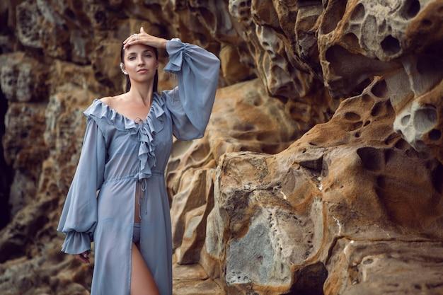 Modna brunetka kobieta w szarej sukience stoi latem na skale z serem