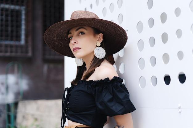 Modna brunetka kobieta z długimi włosami, ubrana w stylowy duży wiklinowy kapelusz, pozująca przy białej ścianie z dziurami.