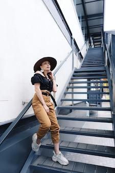 Modna brunetka kobieta z długimi włosami, ubrana w stylowy duży wiklinowy kapelusz, pozuje na schodach.