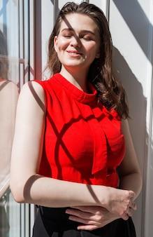 Modna brunetka w czerwonej bluzce pozuje przy oknie i cieszy się słońcem i ciepłem.