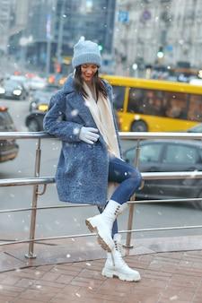 Modna brunetka w płaszczu pozuje w mieście w śnieżną pogodę