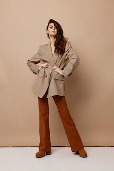 Modna brunetka w płaszczu, spodniach i butach na beżowym tle w studio
