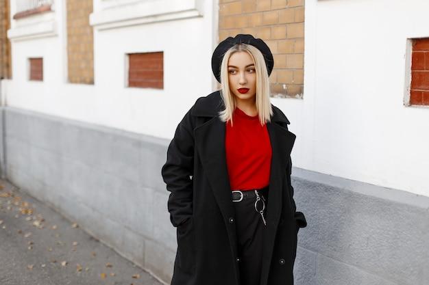 Modna, całkiem nowoczesna młoda blond kobieta w stylowej odzieży wierzchniej w stylu retro z czerwonymi ustami w berecie idzie ulicą w jesienne popołudnie w pobliżu budynku.