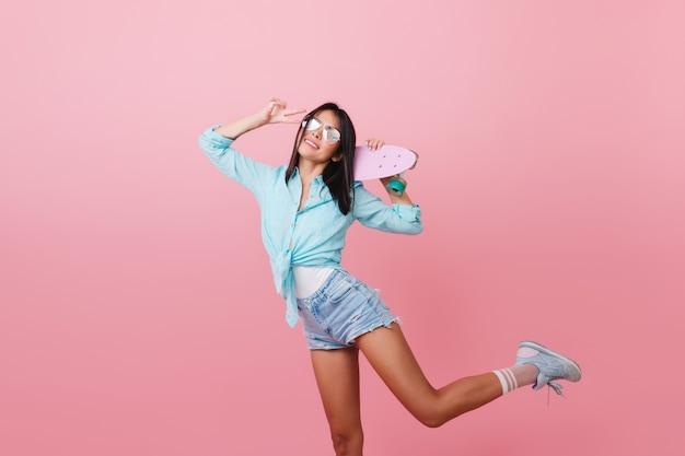 Modna czarnowłosa kobieta z opalenizną, tańcząca z różowym longboardem i śmiejąca się. sportowa azjatycka dziewczyna w niebieskiej koszuli i okularach przeciwsłonecznych stojąc na jednej nodze ze znakiem pokoju.