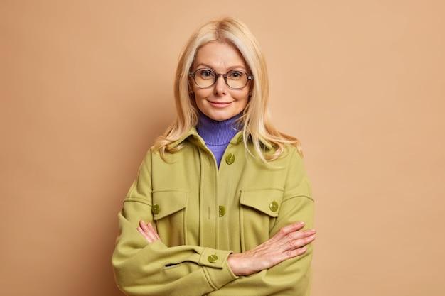 Modna czterdziestoletnia blondynka stoi w asertywnej pozie i trzyma skrzyżowane ręce, nosi przezroczyste okulary i jesienny płaszcz.