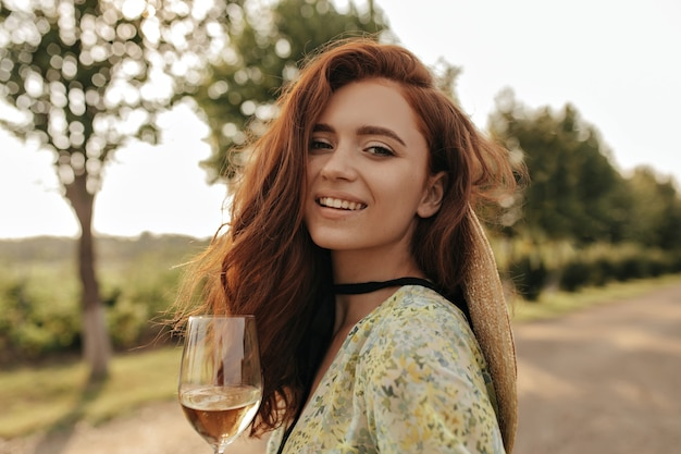 Modna dama z rudą falującą fryzurą i czarnym bandażem na szyi w nowoczesnej zielonej sukience uśmiecha się i trzyma szklankę z napojem na zewnątrz