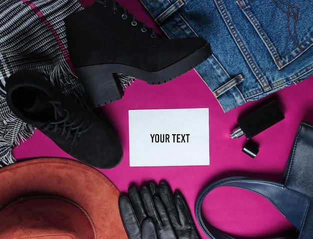 Modna damska odzież, buty, dodatki i biała kartka do wiadomości na czerwonym tle. widok z góry. skopiuj miejsce. płaski styl świecki