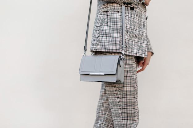 Modna damska szara stylowa torebka. zbliżenie. stylowa dziewczyna w modnych ciuchach w kraciastym garniturze