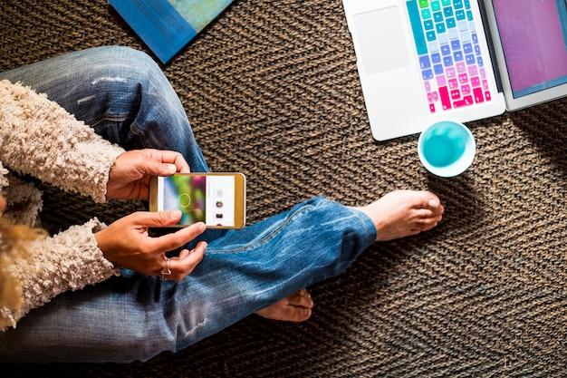 Modna dorosła kobieta siedzi na podłodze i pracuje na czacie z urządzeniami technologicznymi, takimi jak telefon i laptop