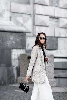 Modna dziewczyna brunetka kurtka i białe spodnie idące przez miasto z czarną torebką i okularami przeciwsłonecznymi.